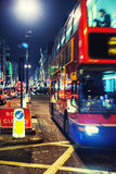 The red double-decker bus in the evening London. The red double-decker bus in London street lights evening Stock Image