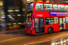 Red double decker bus in motion blur in London night traffic. London, UK - June 19, 2016: red double decker bus in motion blur in London night traffic. The Stock Photos