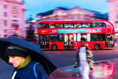 Red double decker bus in motion blur at Piccadilly Circus in London, UK, at night Stock Image