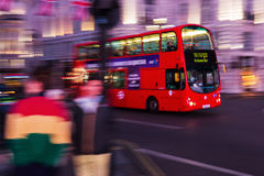 Red double decker bus in motion blur at Piccadilly Circus in London, UK, at night Royalty Free Stock Photography