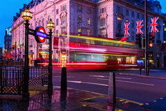 Red double decker bus in motion blur at Piccadilly Circus in London, UK, at night. London, UK - June 19, 2016: red double decker bus in motion blur at Piccadilly Royalty Free Stock Images
