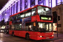 Red double decker bus at night. London, UK – Oct 6, 2011: No 10 London  red double decker bus at night, passing Selfridges Department Store in Oxford Street Stock Image