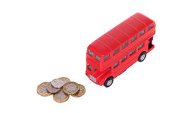 Red double-decker bus with a pile of loose change. Red double-decker bus with a pile of loose sterling change in a concept of the costs of public transport in Royalty Free Stock Image