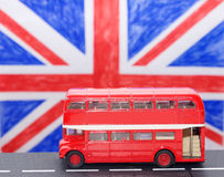 A red double Decker bus. On the road and flag Royalty Free Stock Images
