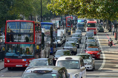 Red double decker buses, London. Red double decker buses and other traffic on October 03, 2014 in London, UK. This buses have become an icon of Britain and are a Royalty Free Stock Image