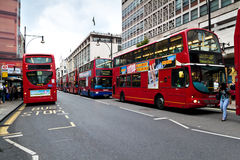 Red double decker buses in Oxford Street. In London.This buses have become an icon of Britain and are a major tourist attraction in themselves Stock Photos