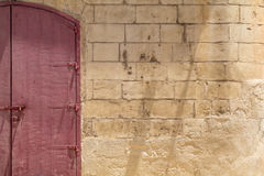 Red double door in yellow limestone wall. Locked red wooden double-door, in Maltese Limestone wall, shot straight-on in Valletta, Malta, Europe. Used in the 2015 Stock Photo