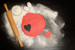Red dough with a carved heart. Eggs and flour on a black table, rolling pin. Royalty Free Stock Photography