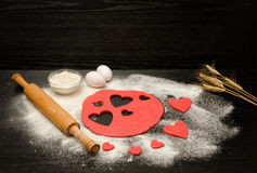 Red dough, cut out hearts, flour, eggs and rolling pin on a black background, ears of wheat, space for text Stock Photography