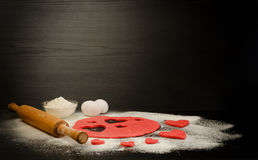 Red dough, cut out hearts, flour, eggs and rolling pin on a black background Stock Photo