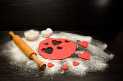 Red dough, cut out hearts, flour, eggs and rolling pin on a black background, space for text Royalty Free Stock Images