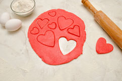 Red dough with a rolling pin and cut out hearts on a white table, close-up.  Stock Photos