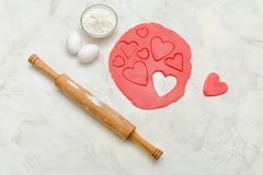 Red dough with a rolling pin and cut out hearts on a white table. Eggs, close-up Royalty Free Stock Images