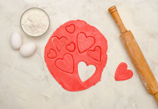 Red dough with a rolling pin and cut out hearts on a white table, eggs, close-up.  Stock Image