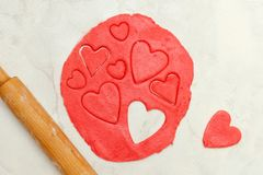 Red dough with a rolling pin and cut out hearts on a white table. Top view Stock Photo