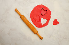 Red dough with a a rolling pin and cut out hearts on a white table. Top view. Space for text Royalty Free Stock Images