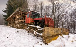 Red dozer in snow near the wood shed. Lovely rural scenery in forest royalty free stock image