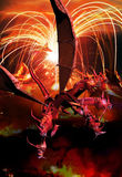 The red dragon. Inspired on the book of Revelations in the Bible, a representation of the red dragon with seven heads and ten horns, on a volvano and fire Royalty Free Stock Image
