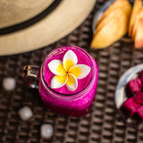 Red Dragon fruit and apple juice in a glass decorated with Plumeria flower. Hat, cut apples and dragon fruit, ice cubes. On a dark Stock Photos