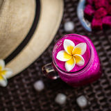 Red Dragon fruit in a glass decorated with Plumeria flower. Hat, ice cubes, cut dragon fruit. On a dark brown surface. Top view. S Stock Image