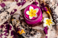 Red Dragon fruit juice in a glass, decorated with Plumeria flower over flowery fabric. Top view. Stock Photo
