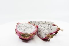 Red dragon fruit slices. Dragon fruit sliced in half and one half sliced in thirds on a white background showing black seeds in white flesh of the fruit royalty free stock photography