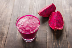 Red dragon fruit smoothie on wooden background. Royalty Free Stock Image