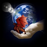 Red dragon on a hand on a background of the earth Stock Photo