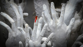 Red Dragonfly on Hands Statue from Hell Stock Photos