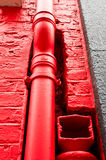Red drainpipe. A red painted metal drainpipe on the outside of a building stock image