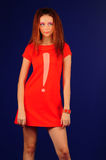 Red dress. The young girl in a red dress in style fashion on a dark blue background Stock Photo