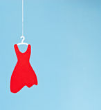 Red Dress. Paper red dress on hanger on sky blue background Royalty Free Stock Image