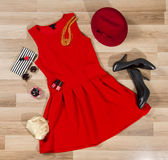 Red dress and accessories arranged on the floor. Woman pleated dress with accessories, purse, hat, high heel shoes and vintage sunglasses Royalty Free Stock Image