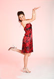 Red dress action girl. Young Adult female in a red batik dress smile and action, one leg up and hands assume to be holding up something Royalty Free Stock Photography
