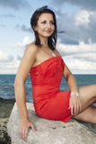 Red dress beauty. Nice lady posing by the sea for portrait and fashion figure photos in Caorle, Italy stock image