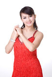 Red dress chinese girl smiling. Red dress chinese girl holding both hands smiling Royalty Free Stock Images