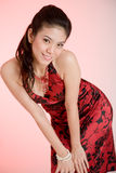 Red dress girl. Sweet oriental girl ina red dress smiling happily Royalty Free Stock Images