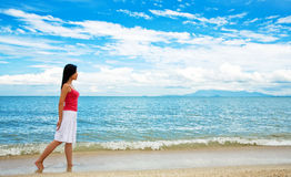 Red dress girl strolling on the beach. Side looking red dress girl strolling on the beach Stock Photography
