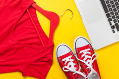 Red dress and gumshoes with laptop Royalty Free Stock Photo