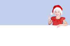 In a red dress and hat of Santa Claus a little girl shows a finger on a billboard Stock Photography