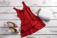 Red dress and heel shoes. Bright evening outfit on shelf. Evening clothes set for women. Plain yet attractive clothing Royalty Free Stock Image
