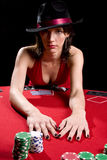 Red dress poker. Attractive woman playing poker at a red poker table wearing red dress Royalty Free Stock Images