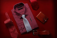Red dress shirt on the red leather. With ties, wallet and belt Royalty Free Stock Photo