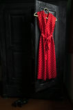 Red dress in a white dots  on a wooden hanger Royalty Free Stock Images