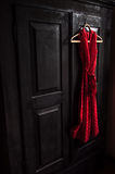 Red dress in a white dots  on a wooden hanger on a black vintage wardrobe Royalty Free Stock Photography