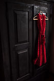 Red dress in a white dots  on a wooden hanger Stock Images