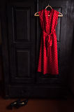Red dress in a white dots  on a wooden hanger Stock Photography