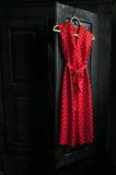 Red dress in a white dots  on a wooden hanger Royalty Free Stock Photography