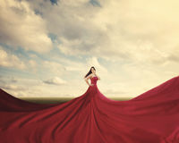 Red dress. A woman standing in a field with a huge red dress royalty free stock image