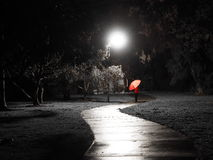 Red dressed pedestrian with red umbrella at a creepy dark bike path lit by street light Stock Image